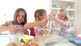 Τρία μικρά κορίτσια που κατασκευάζουν το κέικ από κοινού απόθεμα βίντεο