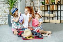 Τρία μικρά κορίτσια συσκεύασαν τα ενδύματά τους σε μια βαλίτσα Έννοια, στοκ εικόνες