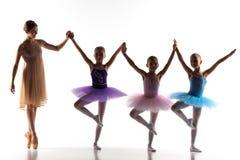Τρία μικρά ballerinas που χορεύουν με τον προσωπικό δάσκαλο μπαλέτου στο στούντιο χορού στοκ εικόνα