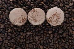 Τρία μπισκότα καφέ βρίσκονται σε μια σειρά στο κέντρο σε ένα υπόβαθρο καφέ σιταριού Στοκ Εικόνες