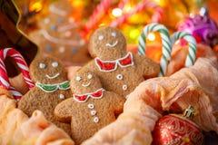Τρία μπισκότα Χριστουγέννων πιπεροριζών στο υπόβαθρο της συμπεριλαμβανόμενης γιρλάντας στην εορταστική ατμόσφαιρα του νέου έτους στοκ φωτογραφίες με δικαίωμα ελεύθερης χρήσης