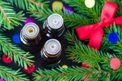 Τρία μπουκάλια των κλάδων ουσιαστικού πετρελαίου και έλατου Χριστούγεννα aromatherapy και έννοια SPA Στοκ Εικόνες