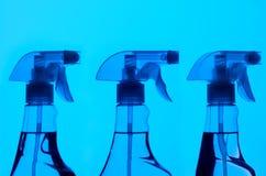 Τρία μπουκάλια ψεκασμού με το μπλε φως στοκ φωτογραφία με δικαίωμα ελεύθερης χρήσης