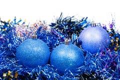 Τρία μπλε σφαίρες και tinsel Χριστουγέννων που απομονώνονται Στοκ Εικόνες