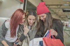 Τρία νέα και όμορφα κορίτσια κρατούν τις τσάντες αγορών και το γ στοκ εικόνες