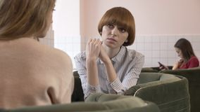 Τρία νέα καυκάσια κορίτσια που κάθονται σε έναν καφέ και που χαμογελούν, ομιλία, διάλογος, συγκίνηση της θλίψης, έννοια κουτσομπο φιλμ μικρού μήκους