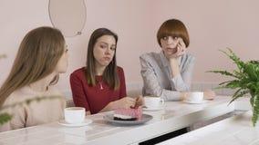Τρία νέα καυκάσια κορίτσια που κάθονται σε έναν καφέ, καφές κατανάλωσης, που τρώει το κέικ, λυπημένος, που με τα χέρια τους, κουτ απόθεμα βίντεο