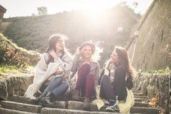 Τρία νέα κορίτσια που κάθονται στα σκαλοπάτια στο δημόσιο πάρκο Thre στοκ εικόνα
