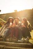 Τρία νέα κορίτσια που κάθονται στα σκαλοπάτια Στοκ Εικόνα