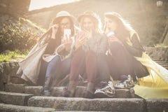 Τρία νέα κορίτσια που κάθονται στα σκαλοπάτια Στοκ Φωτογραφία