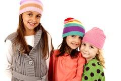 Τρία νέα κορίτσια που φορούν τα χειμερινά καπέλα Στοκ Εικόνες