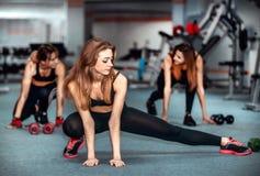 Τρία νέα κορίτσια workout στη γυμναστική στοκ φωτογραφία