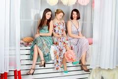 Τρία νέα, όμορφα και κορίτσια συγκίνησης στο φωτεινό χρωματισμένο φόρεμα Στοκ Φωτογραφία