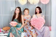 Τρία νέα, όμορφα και κορίτσια συγκίνησης στο φωτεινό χρωματισμένο φόρεμα Στοκ Εικόνες