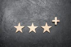 Τρία ξύλινα αστέρια και α συν, σε ένα συγκεκριμένο γκρίζο υπόβαθρο στοκ φωτογραφίες με δικαίωμα ελεύθερης χρήσης