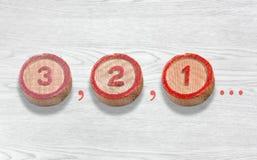 Τρία ξύλινα κομμάτια που απεικονίζουν την αντίστροφη μέτρηση από τρία σε μια Στοκ Φωτογραφίες