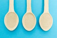 Τρία ξύλινα κουτάλια με τη στιγμιαία ξηρά ζύμη που απομονώνεται σε ένα μπλε υπόβαθρο Η ζύμη είναι το κύριο συστατικό της φρέσκιας στοκ εικόνα με δικαίωμα ελεύθερης χρήσης