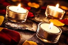 Τρία ο ρομαντικός βαλεντίνος Tealights στην πλάκα με τα ροδαλά πέταλα και βγάζει φύλλα Στοκ φωτογραφία με δικαίωμα ελεύθερης χρήσης