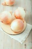 Τρία ολόκληρα κρεμμύδια στον τεμαχίζοντας πίνακα στοκ εικόνα