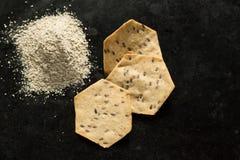 Τρία ολόκληρα οργανικά κροτίδες και αλεύρι σιταριού στο μαύρο φούρνος-π στοκ φωτογραφία
