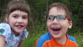Τρία παιδιά γελούν μεταξύ της χλόης απόθεμα βίντεο