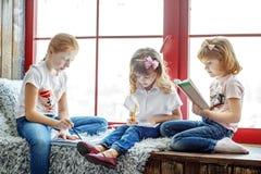 Τρία παιδιά που διαβάζονται, σύρουν και γράφουν Μια ομάδα παιδιών είναι στήριγμα Στοκ Εικόνες