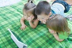 Τρία παιδιά που κοιτάζουν στην ταμπλέτα που βρίσκεται στο κρεβάτι στο σπίτι Χρονικά έξοδα παιδιών Παιδιά που χρησιμοποιούν το μαξ στοκ εικόνα