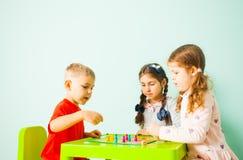 Τρία παιδιά που παίζουν το παιχνίδι του Ludo στο σπίτι στοκ φωτογραφία με δικαίωμα ελεύθερης χρήσης