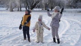 Τρία παιδιά ρίχνουν το χιόνι επάνω στον αέρα απόθεμα βίντεο
