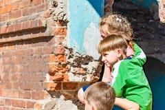 Τρία παιδιά σε ένα σπίτι κρύβουν από τις στρατιωτικές συγκρούσεις, τα παιδιά προσφύγων πάσχουν από την καταστροφή στοκ φωτογραφία με δικαίωμα ελεύθερης χρήσης