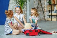 Τρία παιδιά συσκευάζουν τις αποσκευές τους σε μια βαλίτσα Έννοια, πιό lifest Στοκ Εικόνα