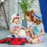 Τρία παιδιά συσκευάζουν τις περιουσίες τους σε μια βαλίτσα Έννοια, lif στοκ φωτογραφίες