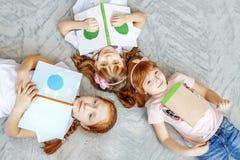 Τρία παιδιά τους σπουδαστές που διαβάζονται τα βιβλία Επίπεδος βάλτε Η έννοια στοκ φωτογραφία