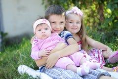 Τρία παιδιά κοντά στα χρώματα Στοκ Εικόνες
