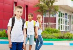 Τρία παιδιά με τα σακίδια κοντά στη σχολική πρόσοψη στοκ εικόνες