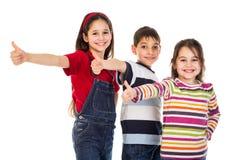 Τρία παιδιά με τους αντίχειρες υπογράφουν επάνω στοκ φωτογραφία