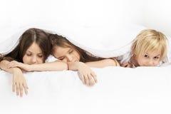 Τρία παιδιά που κοιμούνται στο κρεβάτι στοκ φωτογραφίες