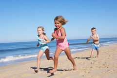 Τρία παιδιά που τρέχουν κατά μήκος της παραλίας Στοκ Εικόνες