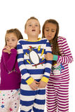 Τρία παιδιά που φορούν τις χειμερινές πυτζάμες με την εκφοβισμένη έκφραση στοκ φωτογραφία