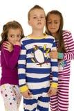 Τρία παιδιά που φορούν τις χειμερινές πυτζάμες δύο κορίτσια φοβισμένα στοκ εικόνα