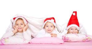 Τρία παιδιά στα καπέλα Χριστουγέννων Στοκ Εικόνες