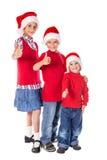 Τρία παιδιά στα καπέλα Χριστουγέννων Στοκ Εικόνα