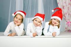 Τρία παιδιά στα καπέλα Χριστουγέννων Στοκ Φωτογραφίες