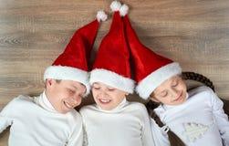 Τρία παιδιά στα καπέλα Santa που βρίσκονται στο ξύλινο υπόβαθρο, που έχει τη διασκέδαση και τις ευτυχείς συγκινήσεις, έννοια χειμ Στοκ Φωτογραφίες