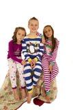 Τρία παιδιά στις ζωηρόχρωμες πυτζάμες που κάθονται σε ένα κάλυμμα στοκ φωτογραφίες με δικαίωμα ελεύθερης χρήσης