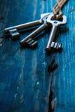 Τρία παλαιά κλειδιά στον ξύλινο πίνακα Στοκ Φωτογραφίες