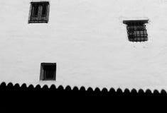 Τρία παράθυρα στην άσπρη σκιά τοίχων και στεγών κατά μήκος της βάσης Στοκ Φωτογραφίες