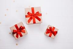 Τρία παρόντα κιβώτια με το κόκκινο τόξο στο ξύλινο υπόβαθρο στοκ εικόνα με δικαίωμα ελεύθερης χρήσης