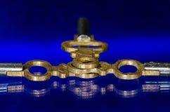 Τρία παλαιά κλειδιά ρολογιών τσεπών ορείχαλκου που βάζουν στην μπλε επιφάνεια Στοκ φωτογραφία με δικαίωμα ελεύθερης χρήσης