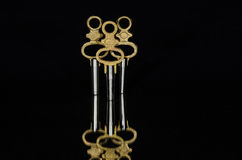 Τρία παλαιά κλειδιά ρολογιών τσεπών ορείχαλκου που στέκονται στο σκοτάδι Στοκ φωτογραφίες με δικαίωμα ελεύθερης χρήσης